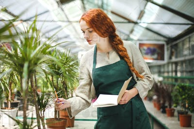 Young florist in apron standing with notepad and pencil in hands while working with plants