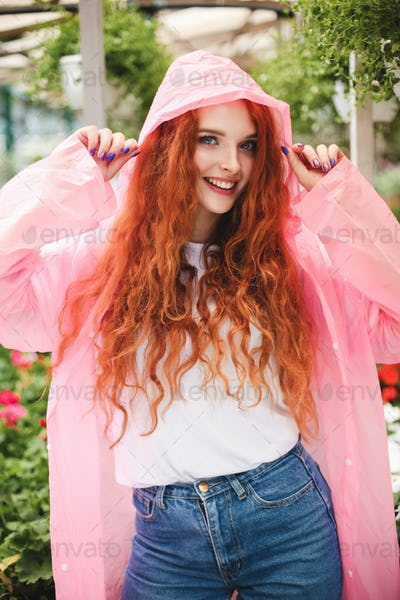Beautiful smiling lady with redhead curly hair standing in pink raincoat