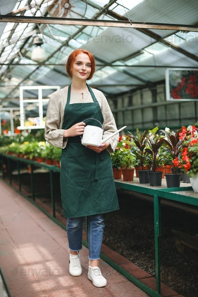 Beautiful florist in apron standing with watering can in hands and joyfully looking in camera