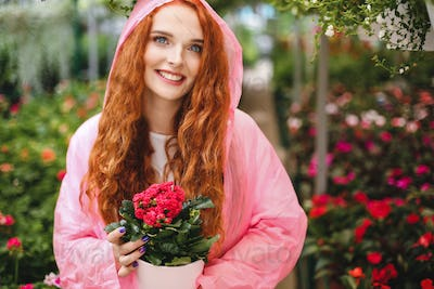 Pretty cheerful lady with redhead curly hair standing in pink raincoat and holding beautiful flower
