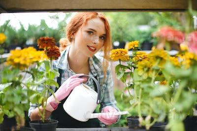 Beautiful florist in apron and pink gloves standing with watering can and dreamily looking in camera