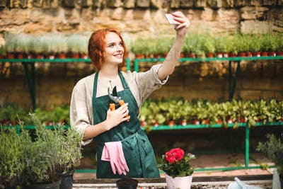 Smiling florist in apron standing with garden scissors and taking photos on frontal cellphone camera