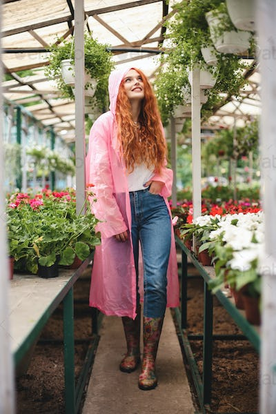 Pretty smiling lady with redhead curly hair walking in pink raincoat and happily aside