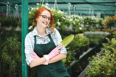 Joyful florist in apron and pink gloves standing with little garden shovel in hand