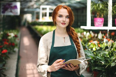 Pretty smiling florist in apron standing with notepad and pencil in hands