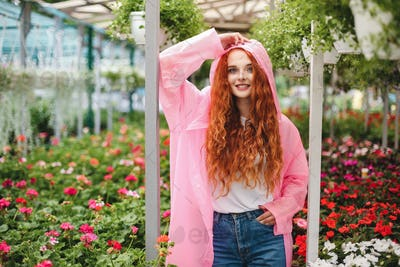 Pretty smiling lady with redhead curly hair standing in pink raincoat