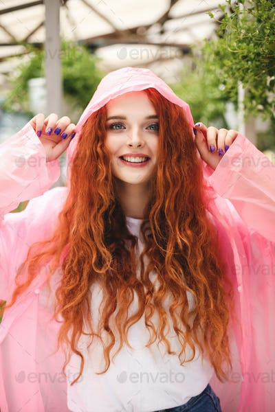 Beautiful lady with redhead curly hair standing in pink raincoat and happily looking in camera