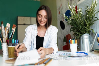 Smiling girl with dark hair sitting at the desk with paintings w