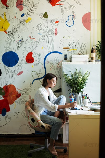 Young beautiful painter in white shirt sitting at the desk dream