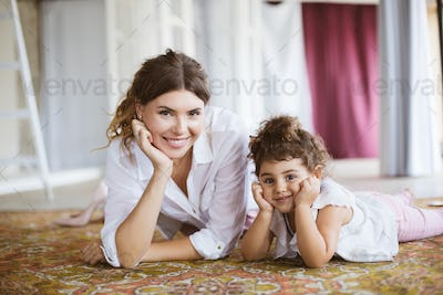 Young smiling mother and pretty little daughter in white shirts