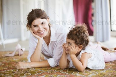 Beautiful smiling mother and cute little daughter in white shirt