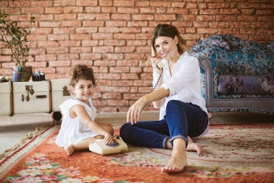 Young smiling mother and little cute daughter happily looking in