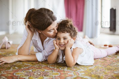 Beautiful mother dreamily kissing cute little daughter lying on