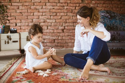 Young pretty mother with little cute daughter dreamily playing w