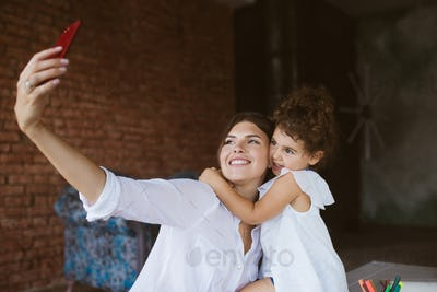 Young mother and cute little daughter hugging while happily taki