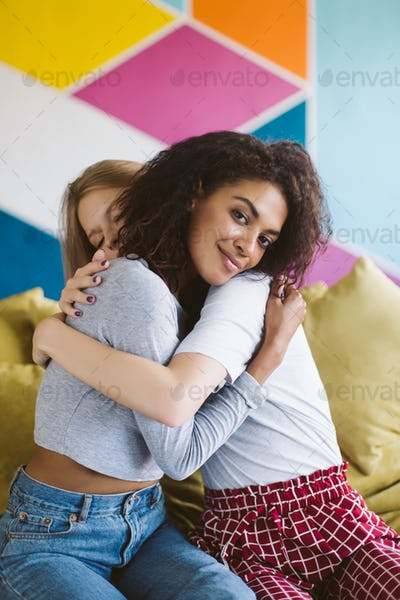 Young smiling african american woman with dark curly hair huggin