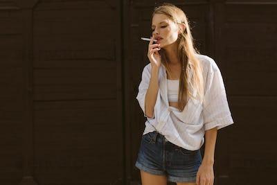 Young beautiful woman in white shirt and denim shorts thoughtful