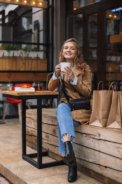 Young cheerful woman in trench coat and jeans happily looking in