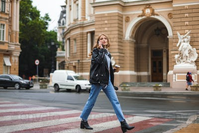 Young beautiful woman in leather jacket and jeans holding cup of