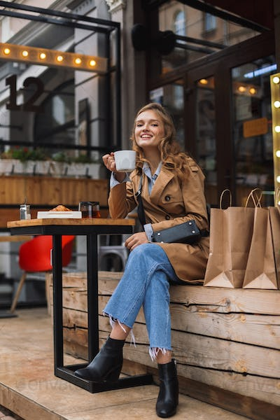 Beautiful smiling girl in trench coat and jeans joyfully looking