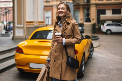 Pretty smiling girl in trench coat with little black cross bag h