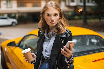 Young beautiful woman in leather jacket holding cup of coffee to
