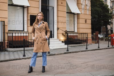 Beautiful pensive girl in trench coat and jeans thoughtfully loo