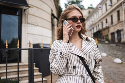 Young pretty woman in striped trench coat with little black cros