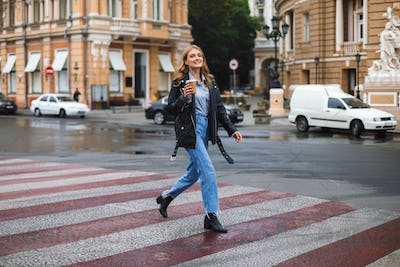 Young beautiful smiling woman in leather jacket and jeans happil
