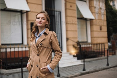 Beautiful smiling girl in trench coat dreamily looking in camera