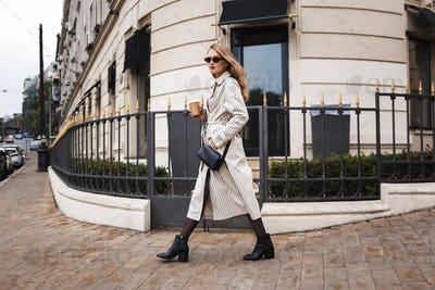 Beautiful girl in striped trench coat and sunglasses with little