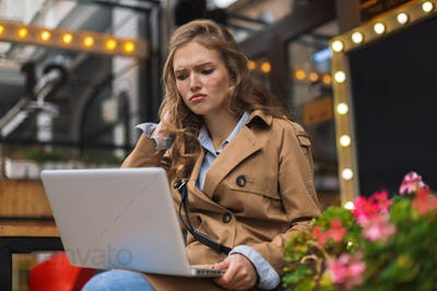 Young upset woman in trench coat working on laptop while spendin