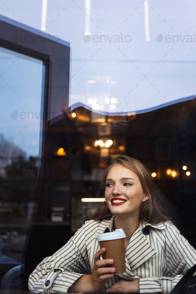 Young beautiful smiling woman in striped trench coat holding cup