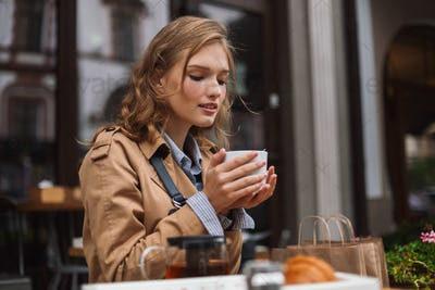 Beautiful girl in trench coat dreamily drinking tea while spendi