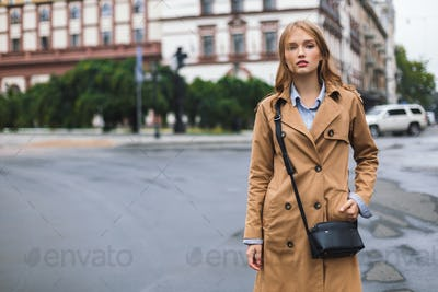 Beautiful pensive girl in trench coat with little black cross ba