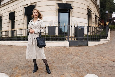 Young pensive woman in striped trench coat with black handbag th