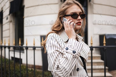 Young serious woman in striped trench coat thoughtfully talking