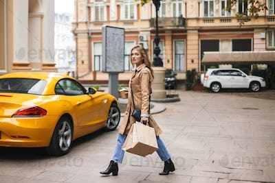 Beautiful girl in trench coat with little black cross bag holdin