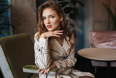 Young beautiful woman with wavy hair in striped trench coat lean