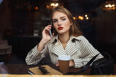Young beautiful woman in striped trench coat talking on cellphon