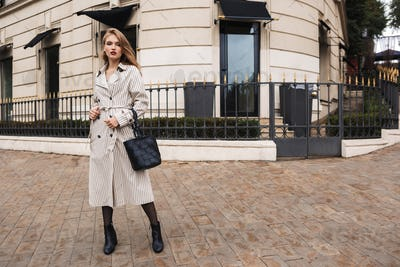 Young attractive woman in striped trench coat with black handbag