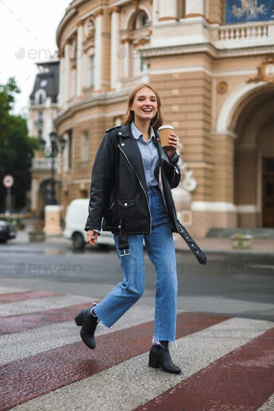 Young cheerful woman in leather jacket and jeans happily looking