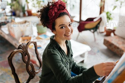 Young pretty smiling woman with dark curly hair sitting on chair