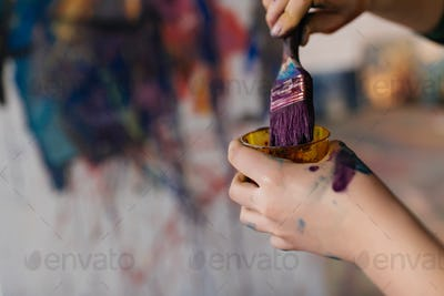 Close up photo of woman hands in paints holding paintbrush drawi