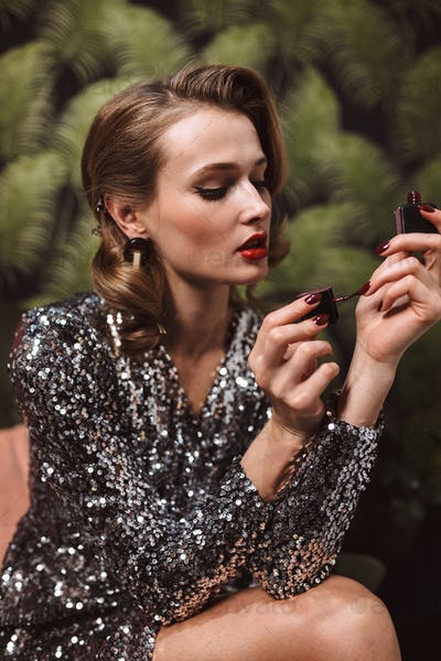 Young beautiful woman with wavy hairstyle and red lips in sequin