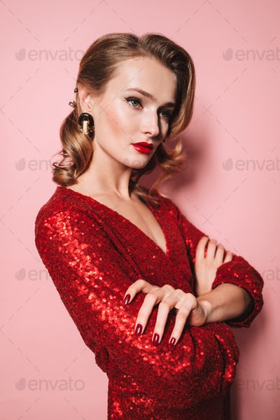 Young beautiful woman with hairstyle in bright red dress thought