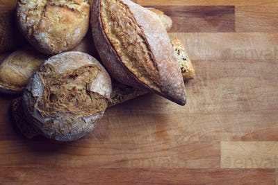 different types of bread on wooden kitchen cutting board