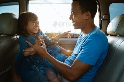 daddy tickling her little girl in the car