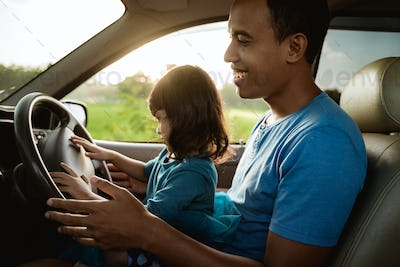 kid playing with steering wheel dad