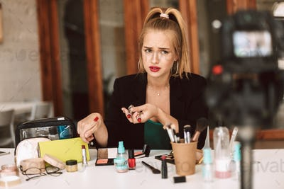 Young beauty blogger confusedly looking aside holding lipsticks